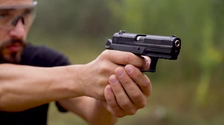 aim : Young man is shooting from a gun, close up