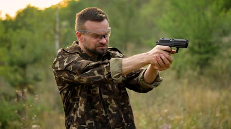 стрельба : Young man in camouflage shooting from a gun, close up. Slow motion