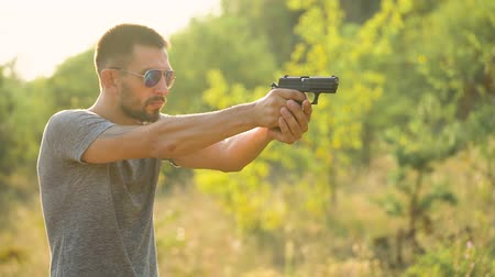 eject : Young man is shooting from a gun, close up