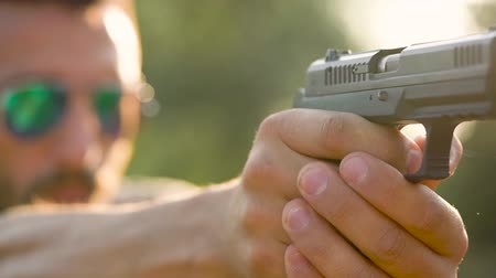 винтовка : Young man is shooting from a gun, close up