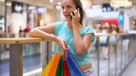 потребитель : Woman with paper bags talking on a smartphone in a shopping center