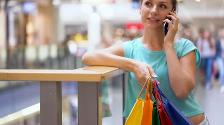 exited : Woman with paper bags talking on a smartphone in a shopping center