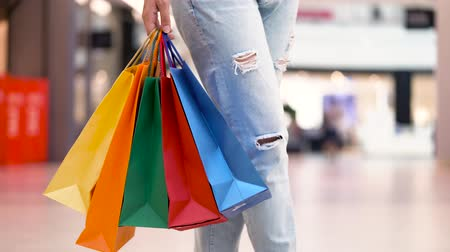 exited : Woman with multi-colored paper bags is walking around the mall Stock Footage