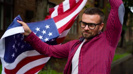 gururlu : Man waving a US flag while walking along the street - the concept of Independence Day USA Stok Video