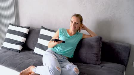 novela : Young, beautiful woman lying on the couch and watching TV. She switches on the remote indefinitely, tracking shot