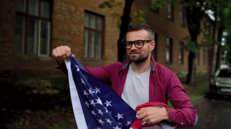 motherland : Man waving a US flag while walking along the street - the concept of Independence Day USA Stock Footage