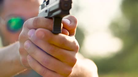 eject : Young man with a gun is aiming to shoot a close up Stock Footage