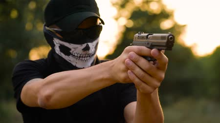 eject : Man with the face closed with a handkerchief and sunglasses getting ready to shoot a gun, close up. Slow motion