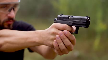 atirar : Young man is shooting from a gun, close up. Slow motion