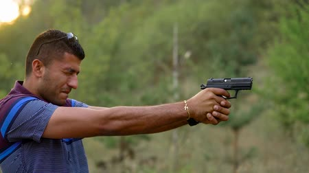 eject : Young arab man is shooting from a gun, close up. Slow motion Stock Footage
