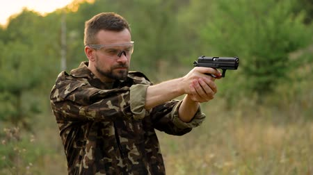 калибр : Young man in camouflage shooting from a gun, close up. Slow motion