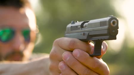 snajper : Young man is shooting from a gun, close up. Slow motion