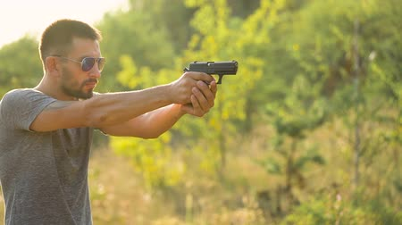 eject : Young man is shooting from a gun, close up. Slow motion