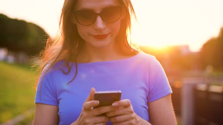 receber : Woman in sunglasses using a smartphone outdoors at sunset