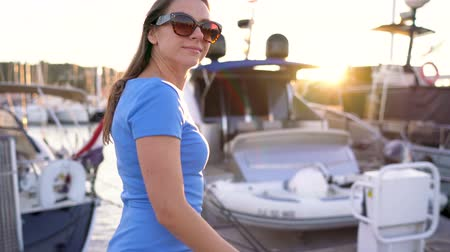 luxury yacht : Woman in sunglasses walking along the dock with a lot of yachts and boats at sunset, close up