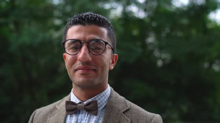 szerény : Portrait of a young Arab smiling man in glasses. Slow motion
