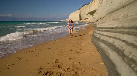 купаться : Beach bikini woman carefree running along the water on the beach. Picturesque sea coast of Corfu, Greece. Slow motion