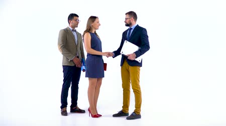 desgaste formal : Group of three business partners shake hands welcoming each other in studio Vídeos