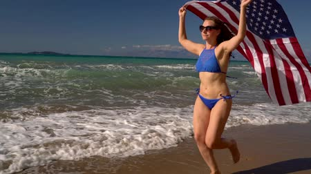 motherland : Beach bikini woman with US flag running along the water on the beach. Concept of Independence Day USA. Slow motion Stock Footage