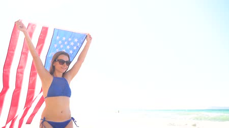гордый : Beach bikini woman with US flag carefree walking along the water on the beach. Concept of Independence Day USA