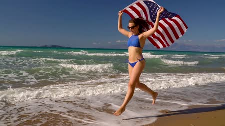 motherland : Beach bikini woman with US flag running along the water on the beach. Concept of Independence Day USA