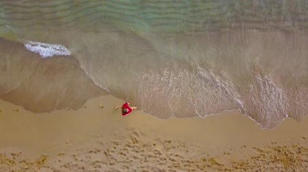 ślady stóp : Top view of a woman walking barefoot along wet sand beach. Running wave is washing away footprints on the sand Wideo