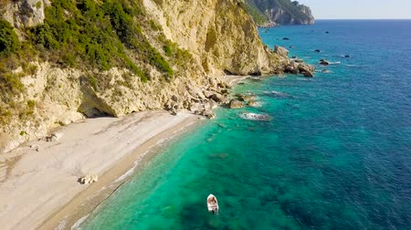 motor boat : Aerial view of a boat in front of the Corfu island in Greece. Amazing beach with a turquoise and transparent sea Stock Footage