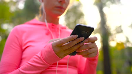 athletes foot : Woman with headphones and a smartphone chooses the music for a run through the autumn park Stock Footage