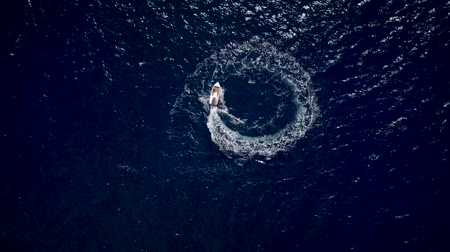 hajózik : Aerial view of a motor boat designing a circle in the sea navigating fast
