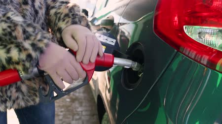 filling station : Woman fills petrol into her car at a gas station in winter Stock Footage