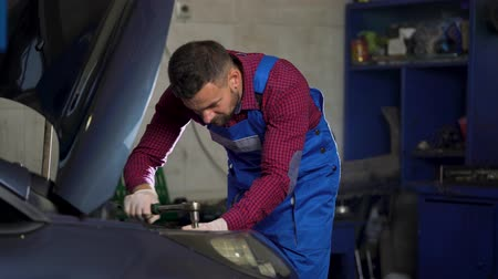 İngiliz anahtarı : Car service, repair, maintenance and people concept - auto mechanic working at workshop Stok Video
