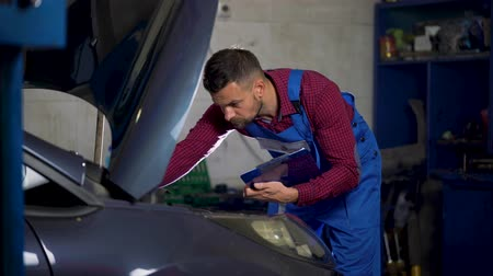 İngiliz anahtarı : Car service, repair, maintenance and people concept - mechanic checks the quality of the work performed Stok Video