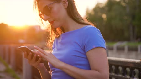 correspondência : Woman in sunglasses using a smartphone outdoors at sunset
