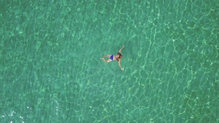 солнечные ванны : View from the height on swimming woman in the clear sea