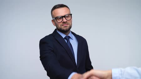 podání ruky : Two business partners shake hands welcoming each other in studio. Slow motion Dostupné videozáznamy