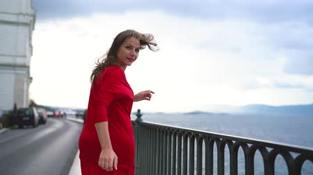 hayran olmak : Woman in red dress runs along the waterfront on the sea coast