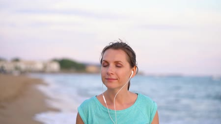 sobre : Athletic woman with headphones walking along the beach. Video at different speeds - normal and slow