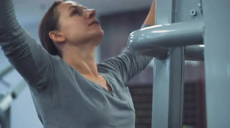 pulling up : Woman does pull-ups on gravitron for strengthening the shoulder muscles in the gym