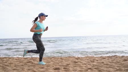 závazek : Athletic woman running along the beach