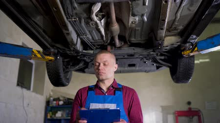 csavarkulcs : Car service, repair, maintenance and people concept - mechanic checks the quality of the work performed Stock mozgókép