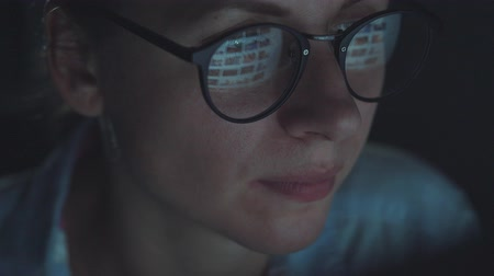 looking distance : Woman in glasses looking on the monitor and surfing Internet Stock Footage