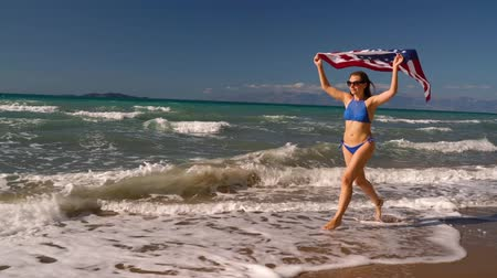 motherland : Beach bikini woman with US flag running along the water on the beach. Concept of Independence Day USA. Slow notion