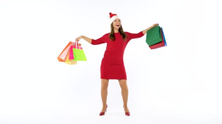 barganha : Christmas female shopper holding multicolored shopping bags and crazy dancing on white background in studio. Lets go holiday shopping concept