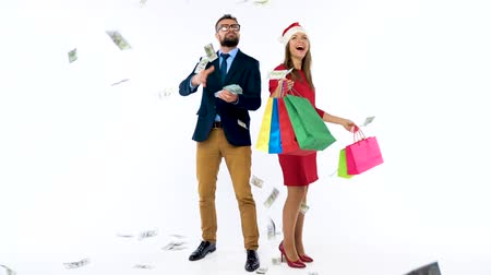 зарабатывать : Dollars falling on formally dressed man and woman in the Santa Claus hat. Lets go holiday shopping and celebrate concept.