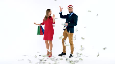 allowance : Dollars falling on formally dressed man and woman in the Santa Claus hat. Lets go holiday shopping and celebrate concept.