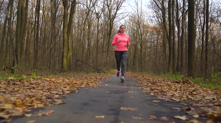 recreational park : Close up of woman with headphones and smartphone running through an autumn forest at sunset. Slow motion