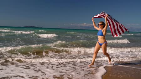 motherland : Beach bikini woman with US flag running along the water on the beach. Concept of Independence Day USA. Stock Footage