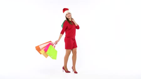 alku : Christmas female shopper holding multicolored shopping bags on white background in studio. Lets go holiday shopping concept