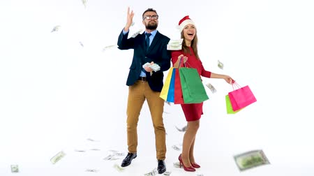 allowance : Dollars falling on formally dressed man and woman in the Santa Claus hat. Lets go holiday shopping and celebrate concept. Slow motion Stock Footage