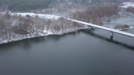 gát : View from height to the bridge on which cars are traveling over the river in winter Stock mozgókép